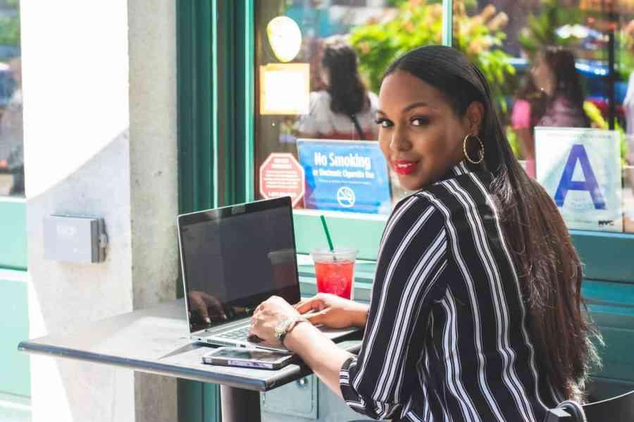 Imagem de uma mulher utilizando a conexão Wi-Fi em um cybercafé.