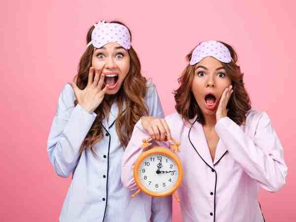 Na foto duas mulheres de pijama segurando um relógio.