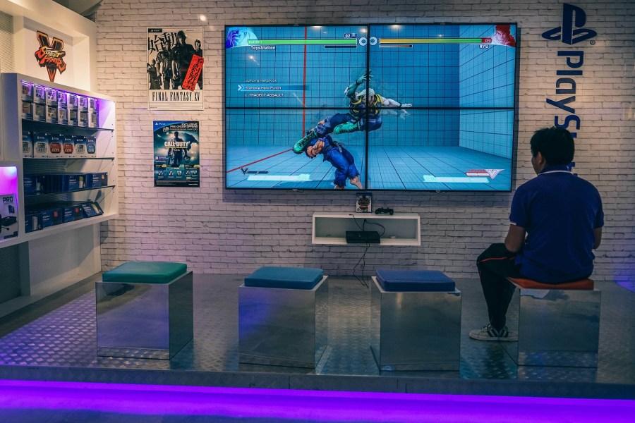 Imagem de homem jogando uma partida de luta em um quarto com decoração gamer