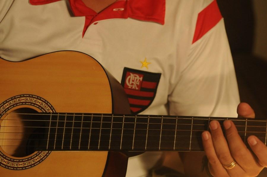 Imagem de homem tocando violão com uma camisa do Flamengo