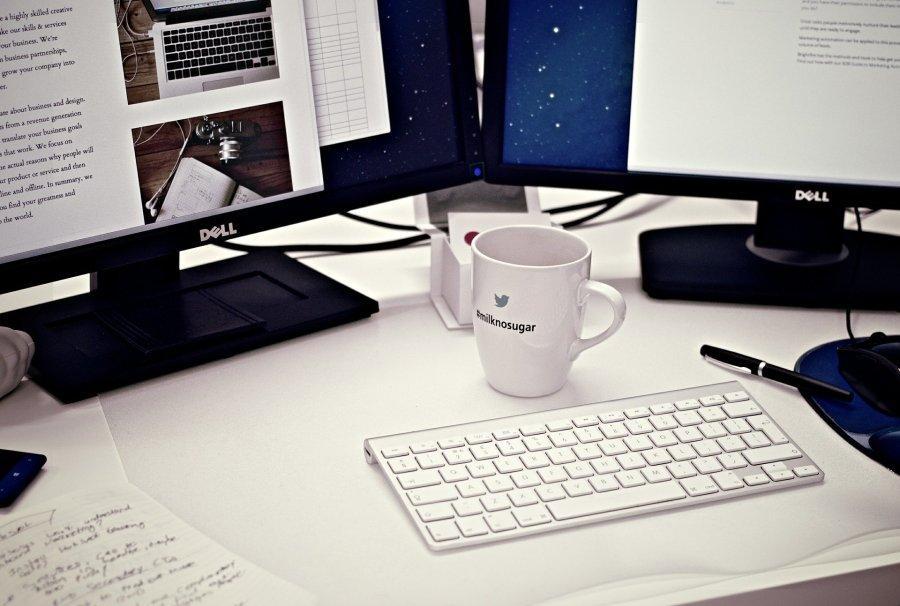 Dois monitores, teclado e xícara.