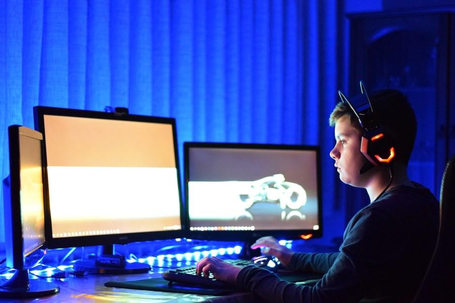 Menino jogando com três monitores.