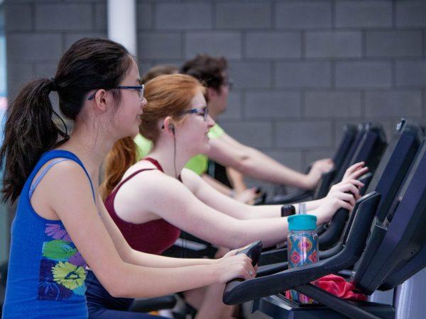 Imagem mostra uma fileira de pessoas usando bicicletas ergométricas horizontais numa academia.