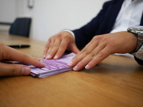 Detalhe de mão de pessoa passando um monte de dinheiro em espécie para a mão de um homem.