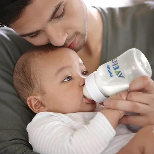 Pai dando mamadeira para o bebê com uma mamadeira Avent