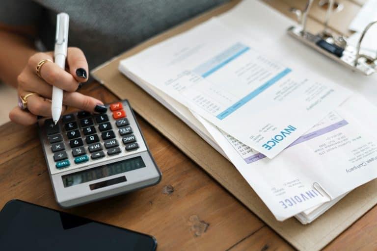 Mão de mulher segurando uma caneta e digitando na calculadora, com prancheta com folhas de papel ao lado.