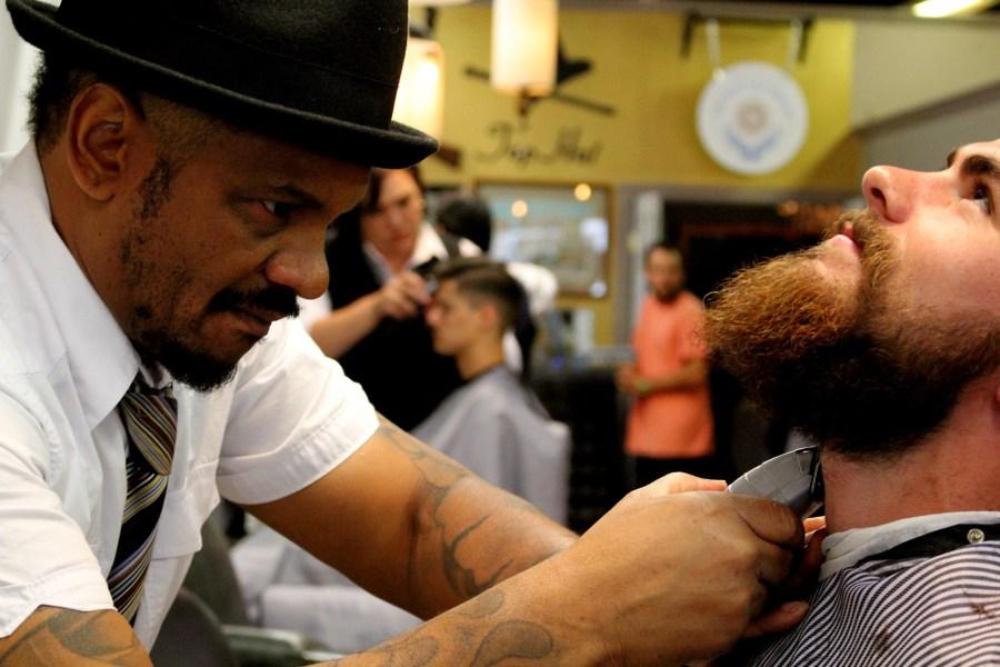 Homem fazendo a barba do cliente.