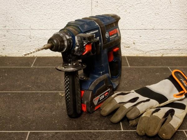 Imagem mostra uma furadeira Bosch ao lado de um par de luvas.