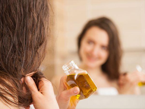 Imagem de uma mulher segurando um frasco de óleo, olhando para o espelho.
