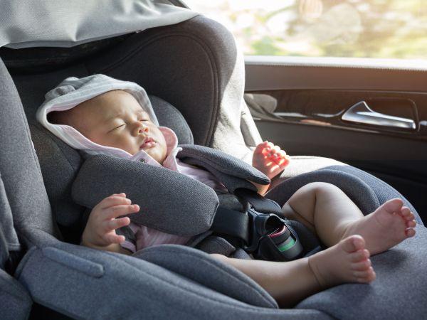 Bebê dormindo em bebê conforto dentro do carro.