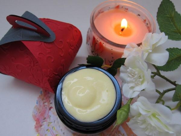 Imagem de creme anti-idade junto a vela aromática e flores.