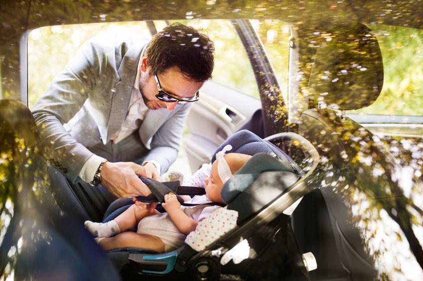 Pai colocando filha em bebê conforto no carro.
