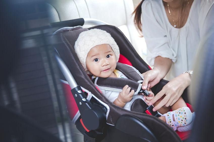 Mãe ajustando bebê em seu bebê conforto dentro do carro.