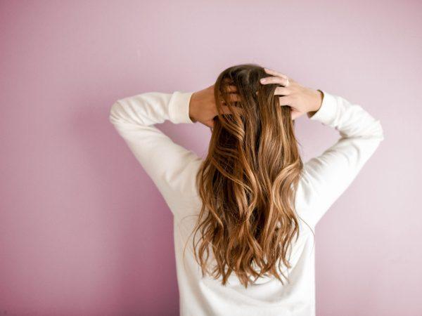 Mulher de costas com as mãos nos cabelos.