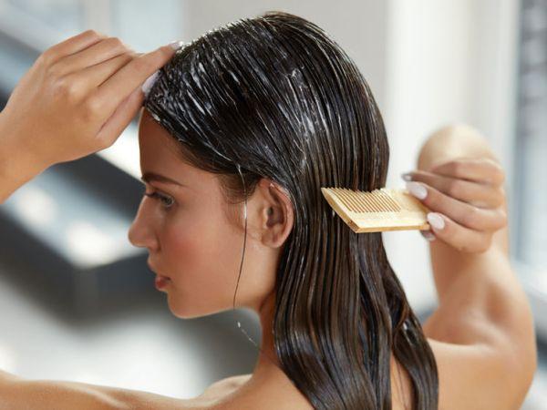 Imagem de uma mulher aplicando máscara de tratamento no cabelo.