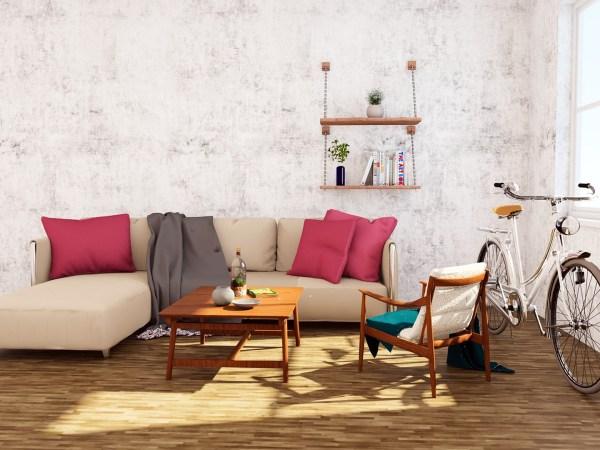 Na foto um sofá com uma mesa de centro e uma poltrona ao lado de uma bicicleta.