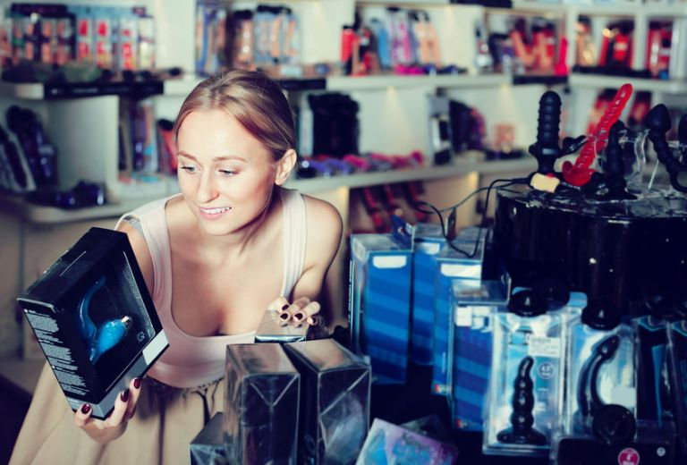 Imagem de mulher escolhendo strap on em loja de produtos eróticos
