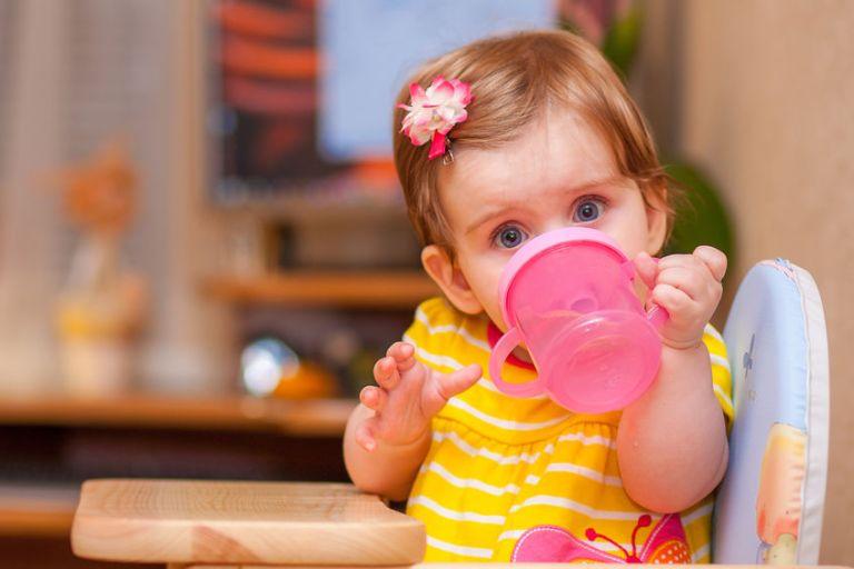 Menina sentada em sua cadeirinha de alimentação bebendo em copo de transição cor de rosa e olhando para a câmera.