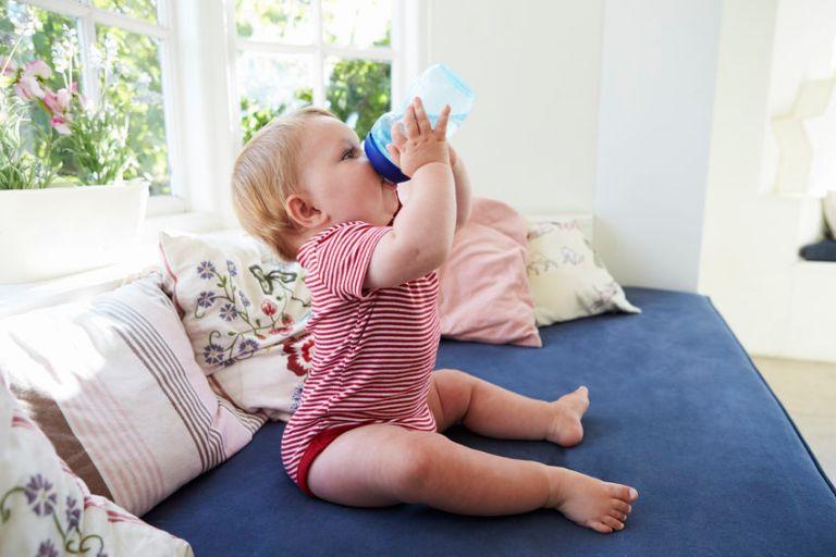 Bebê bebendo água em seu copo de transição sem alça.