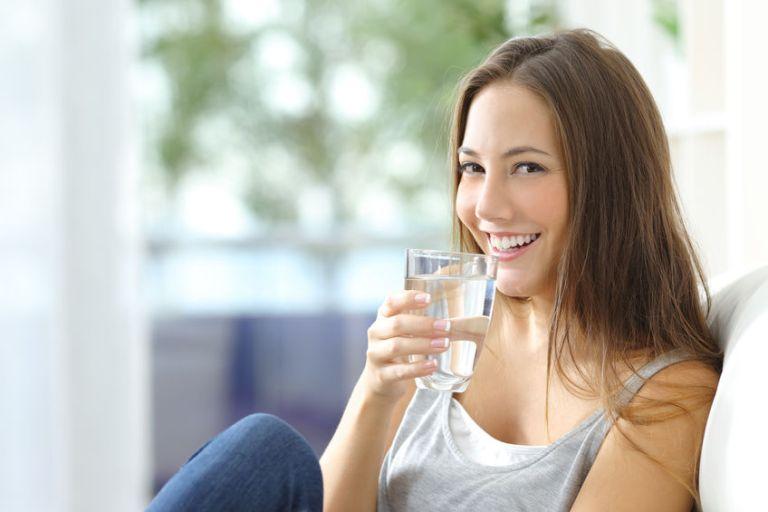 Imagem de uma mulher tomando um copo d'água.