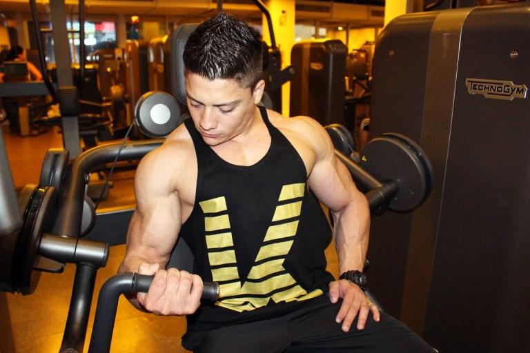 Homem na academia fazendo musculação.