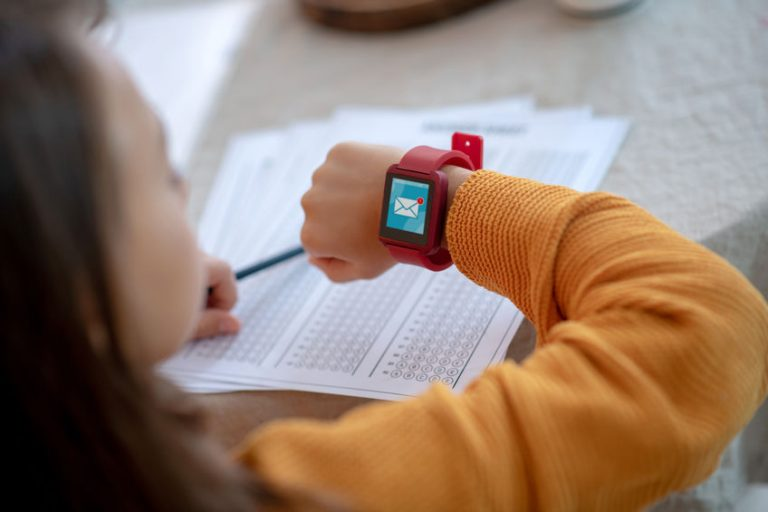 Little girl looking at the children's smartwatch while studying.