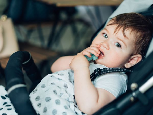 Little boy with beautiful eyes sitting in a baby carriage