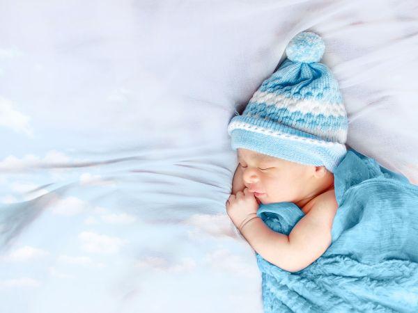 Newborn baby boy sleeping in busket waering black & brown hat and blanket isolated in white background