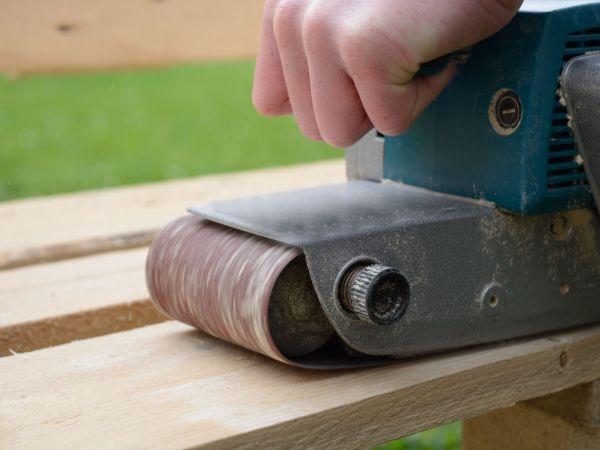 Person grinds Handheld belt sander softwood