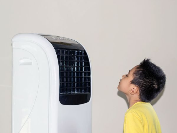 Because of the hot weather, the boy stood by the fan blowing cold air to his face.