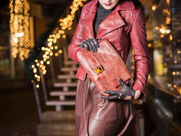 Shopping lady is holding luxury brown shiny bag in her hands shopping concept