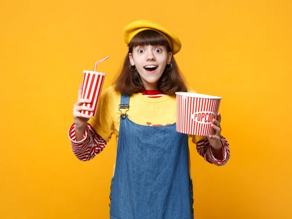 Excited girl teenager in french beret, denim sundress hold plastic cup of cola or soda, bucket of popcorn isolated on yellow background. People sincere emotions, lifestyle concept. Mock up copy space