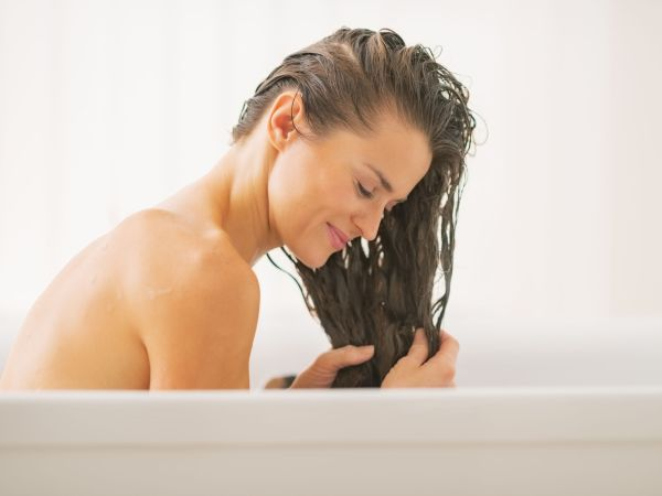 Happy young woman washing hair in bathtub