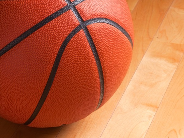 An orange basketball sits on a hardwood court floor with spot lighting and background that goes from dark to light.