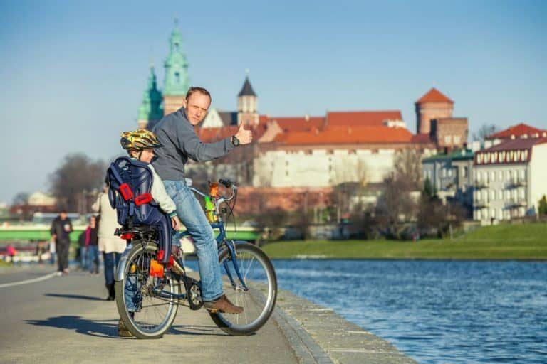Padre in bici con figlio nel seggiolino