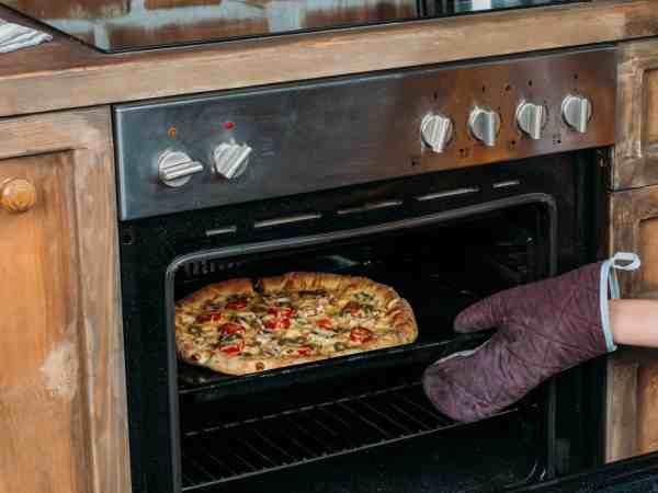 Pizza che viene tirata fuori da un forno