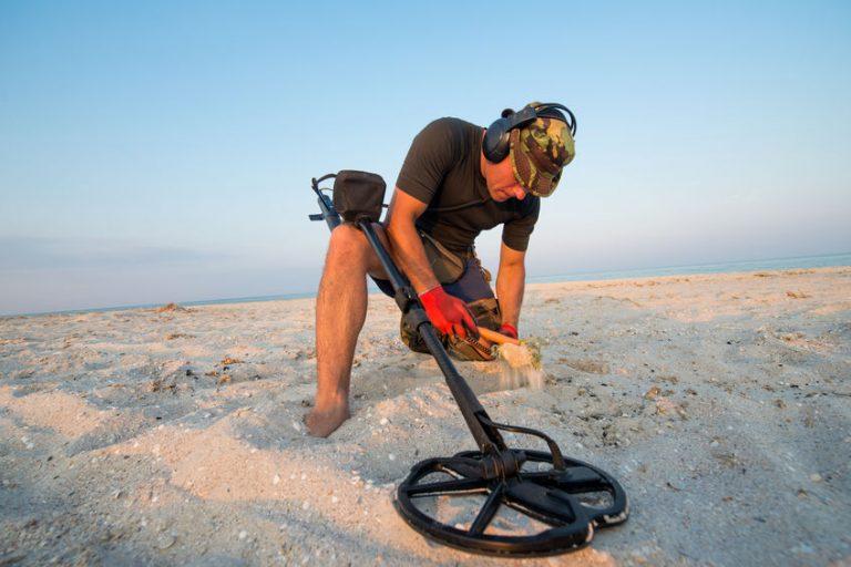Uomo con metal detector in cerca di tesori