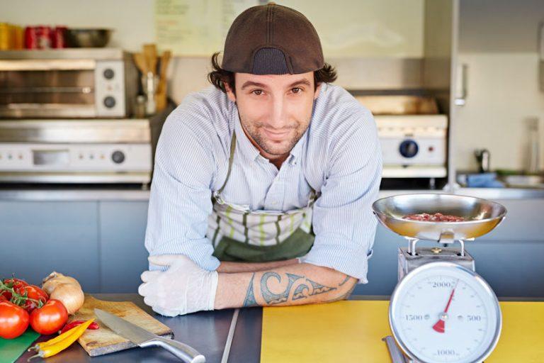 Uomo in cucina accanto a una bilancia meccanica