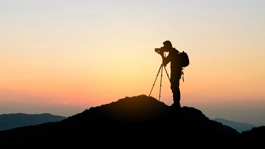 Person standing on mountain top with travel photography gear, taking a landscape photograph