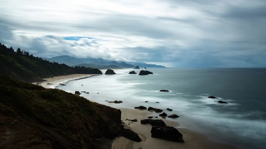 landscape scene of a beach, ocean, and scenic mountains