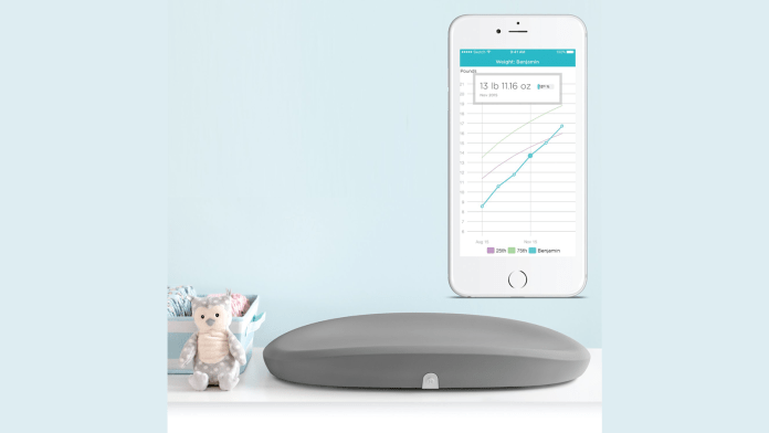Hatch Baby Grow Smart Changing pad on table next to cute baby toys and companion mobile app on smartphone