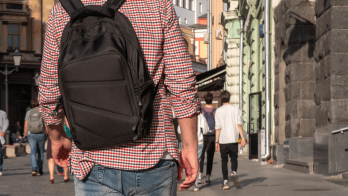 Person walking down a city street wearing a black backpack
