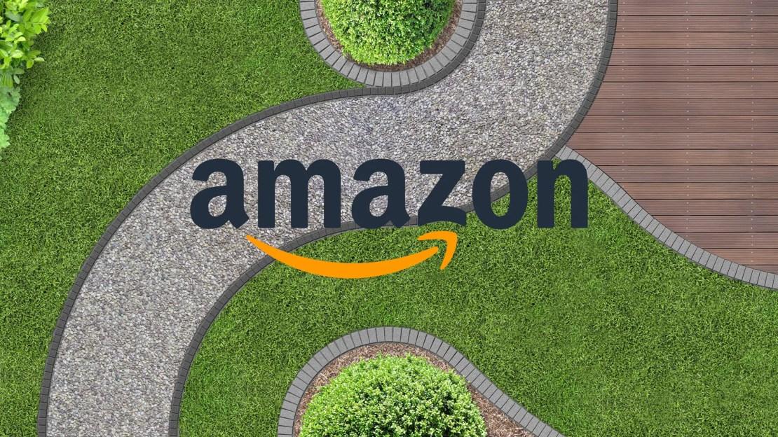 An Amazon logo overtop a sidewalk winding through a garden.