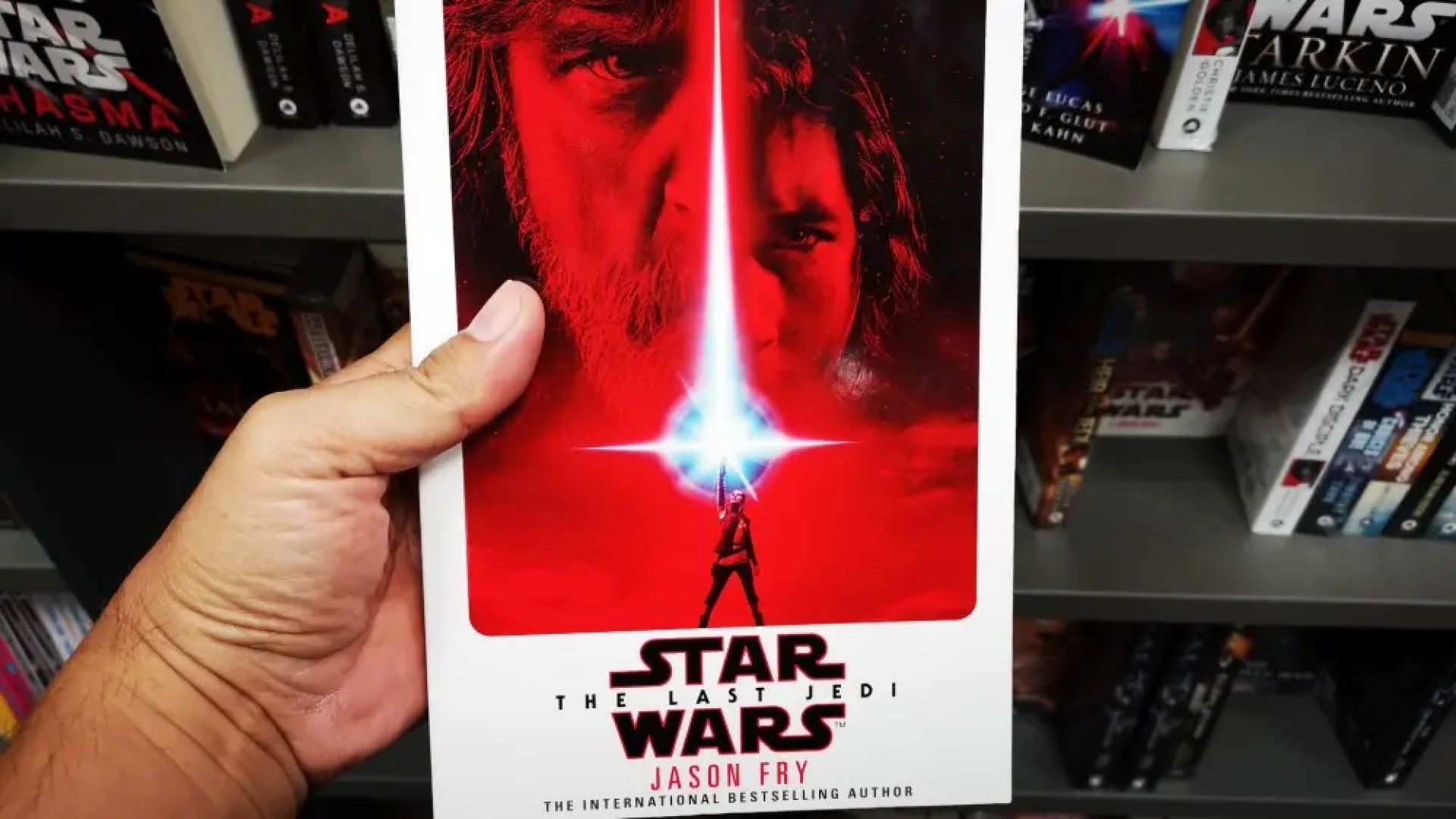 """Hand holding """"Star Wars: The Last Jedi"""" book by author Jason Fry in a bookstore"""