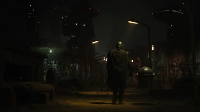 The Mandalorian walking down a dark and dirty city.