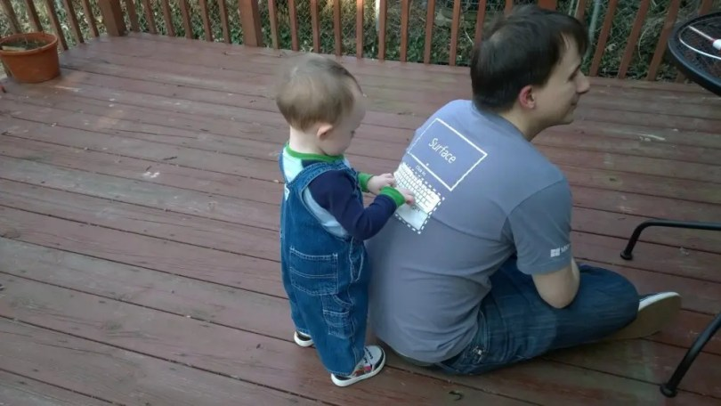 """A young boy """"typing"""" on the image of a Surface keyboard on the author's back."""