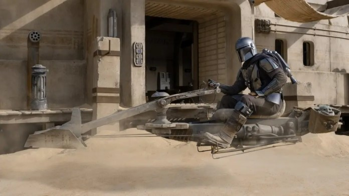 The Mandalorain on a speeder bike, with the Child in a cargo container.
