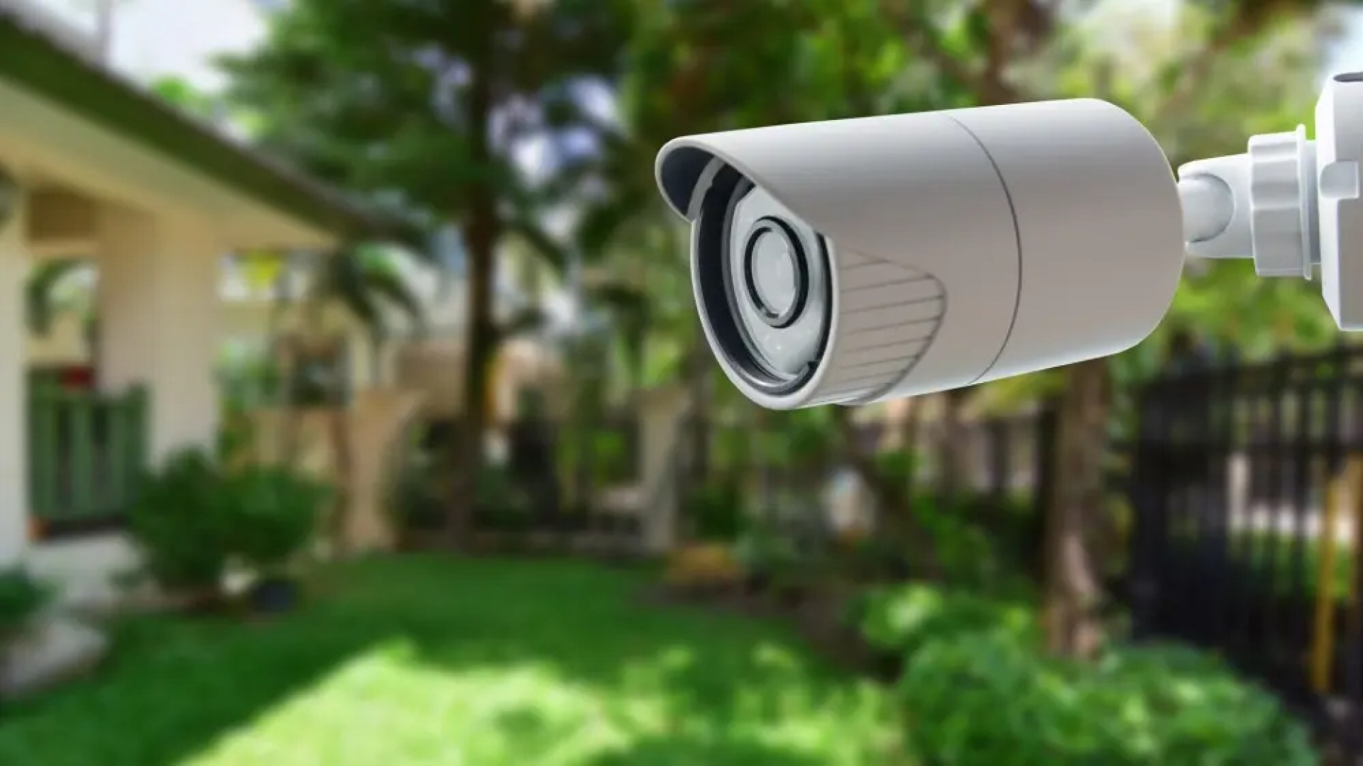 A security camera mounted outside overlooking a backyard