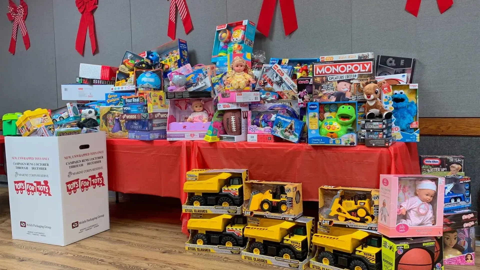 A Toys for Tots table that's overflowing with toys.