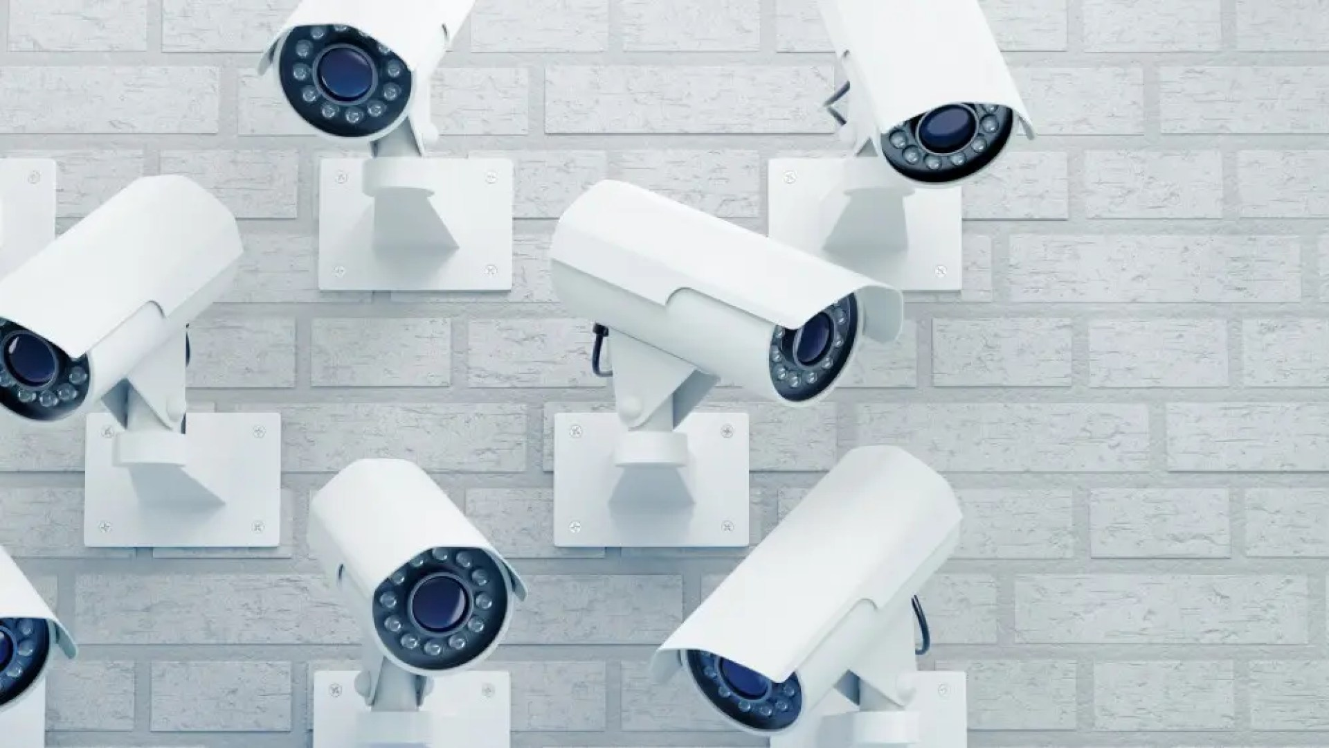 Group of external surveillance cameras mounted on a brick wall.